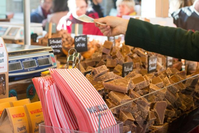 A customer paying cash money for fudge in Borough Market, London
